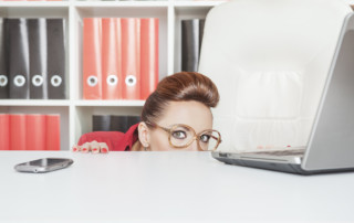 LLI Leadership Styles Introvert and Extrovert -Business Woman Hiding Behind Table And Afraid