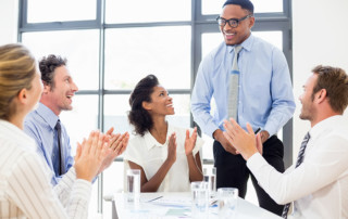 LLL-Leading with Vulnerability-Business team applauding a colleague in meeting