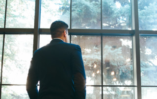 Lonely man standing near window. Prosperous businessman. Success and wealth concept. Authority.