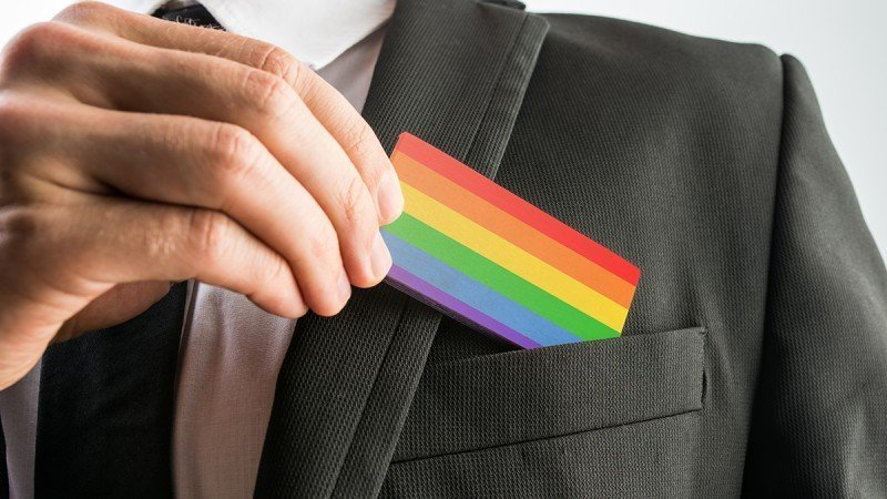 Cultivating Workplace Cultures of Belonging-Rhodes Perry-Man withdrawing a wooden card painted as the gay pride flag