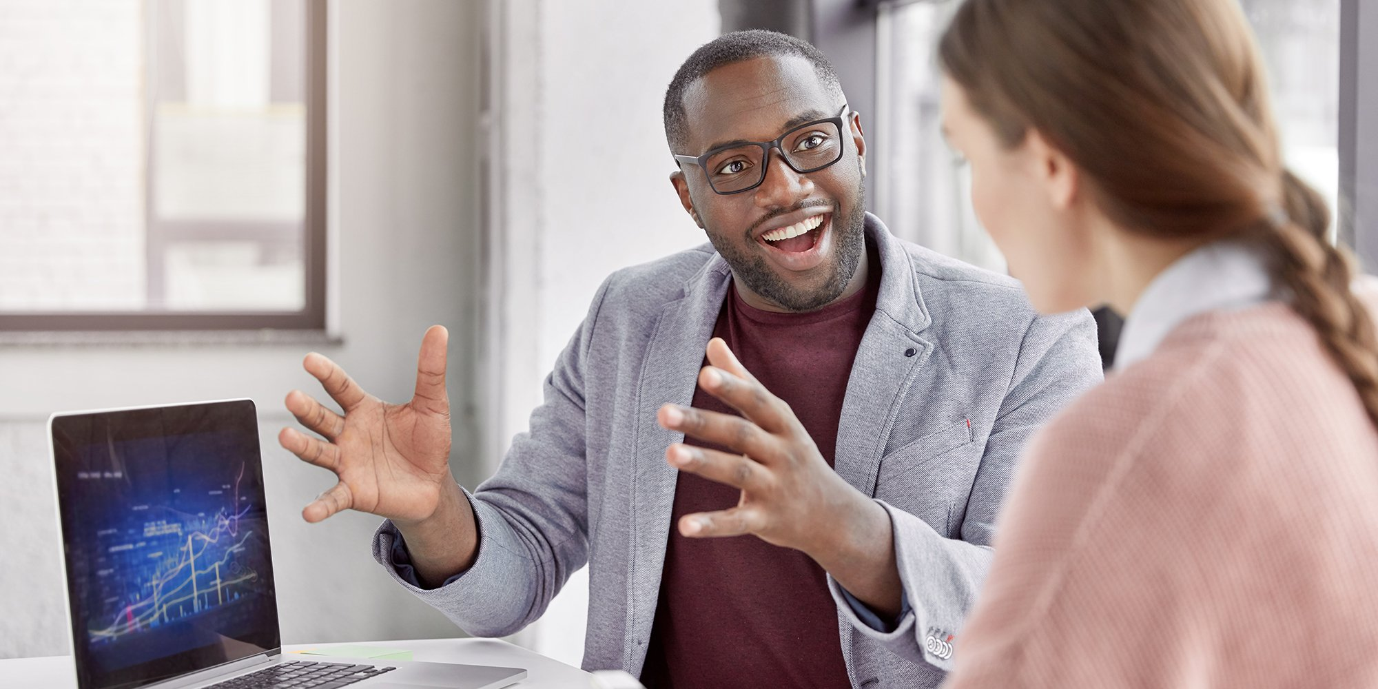 Fundamentals of Coaching-Cheerful African American male boss listens to his female secretary with happy expression, rejoices achievement great success and showing high results on business market, work at new startup