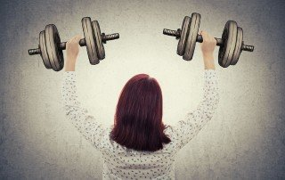 LLI Building Muscles-Rear view of a young, professional businesswoman in suit lifting imaginary sketched dumbbell weights. Business training, strength and success concept isolated on grey wall background.